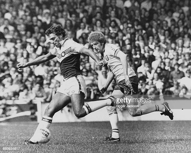 Trevor Brooking of West Ham United prepares to shoot as Doug Evans of Norwich City chases him down during their English League Division One match on...