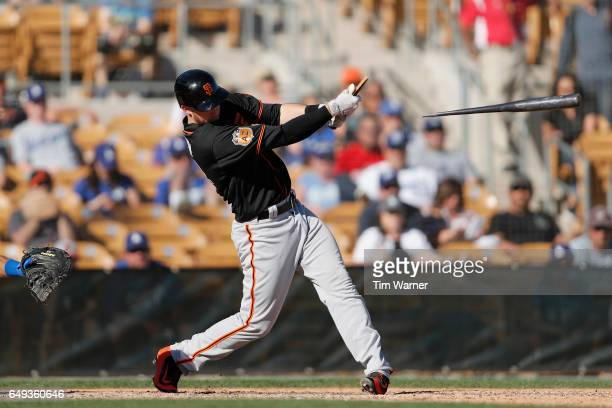 Trevor Brown of the San Francisco Giants breaks his bat in the ninth inning during the spring training game against the Los Angeles Dodgers at...