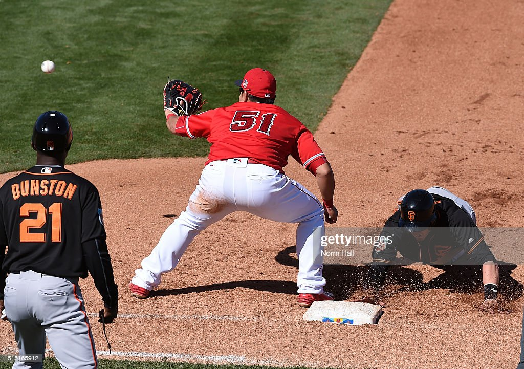 Trevor Brown #14 of the San Francisco Giants dives back to first base as Ji-Man Choi #51 of the Los Angeles Angels of Anaheim waits for the throw over during the fifth inning at Tempe Diablo Stadium on March 12, 2016 in Tempe, Arizona.