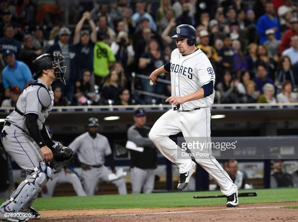 Trevor Cahill of the San Diego Padres runs as he scores ahead of the throw to Tony Wolters of the Colorado Rockies during the sixth inning of a...