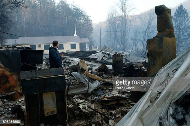 Trevor Cates walks through the smoldering remains of the fellowship hall of his church the Banner Missionary Baptist Church as he inspects damage...