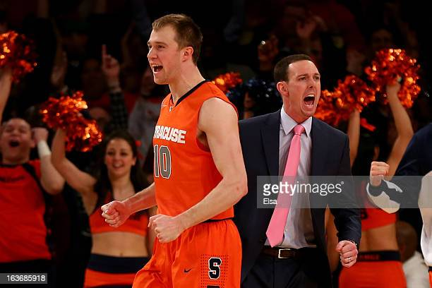 Trevor Cooney and assistant coach Gerry McNamara of the Syracuse Orange react after CJ Fair made a 3point basket at the buzzer of the end of the...
