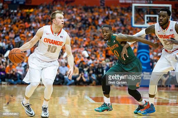 Trevor Cooney of the Syracuse Orange dribbles during the first half as Ja'Quan Newton of the Miami Hurricanes is defended by Rakeem Christmas of the...