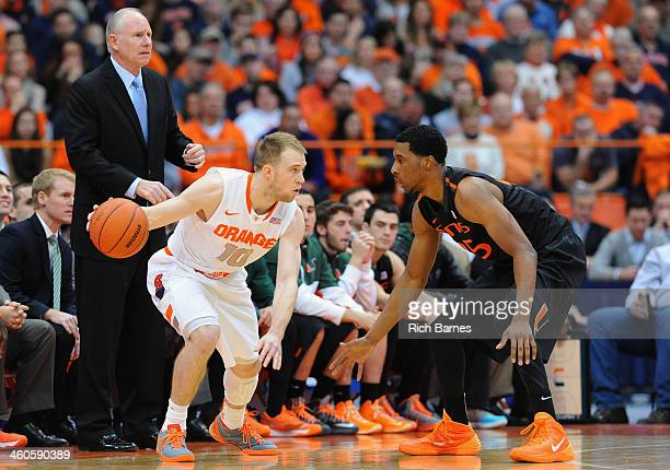 Trevor Cooney of the Syracuse Orange drives to the basket around the defense of Garrius Adams of the Miami Hurricanes as head coach Jim Larranaga of...