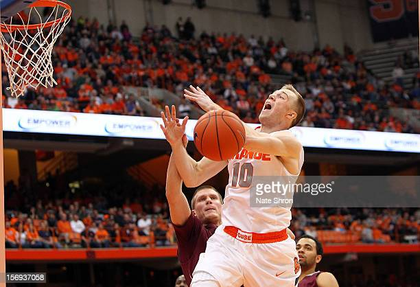 Trevor Cooney of the Syracuse Orange loses the ball as he drives to the basket against Pat Moore and Damon ShermanNewsome of the Colgate Raiders...