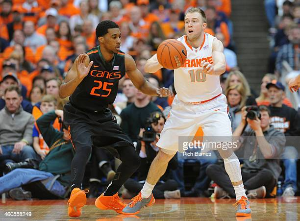 Trevor Cooney of the Syracuse Orange passes the ball around the defense of Garrius Adams of the Miami Hurricanes during the first half at the Carrier...