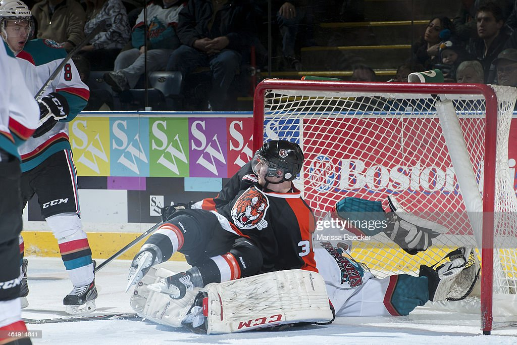 Trevor Cox #36 of the Medicine Hat Tigers collides with Jordon Cooke #30 of the Kelowna Rockets during the third period on January 24, 2014 at Prospera Place in Kelowna, British Columbia, Canada.