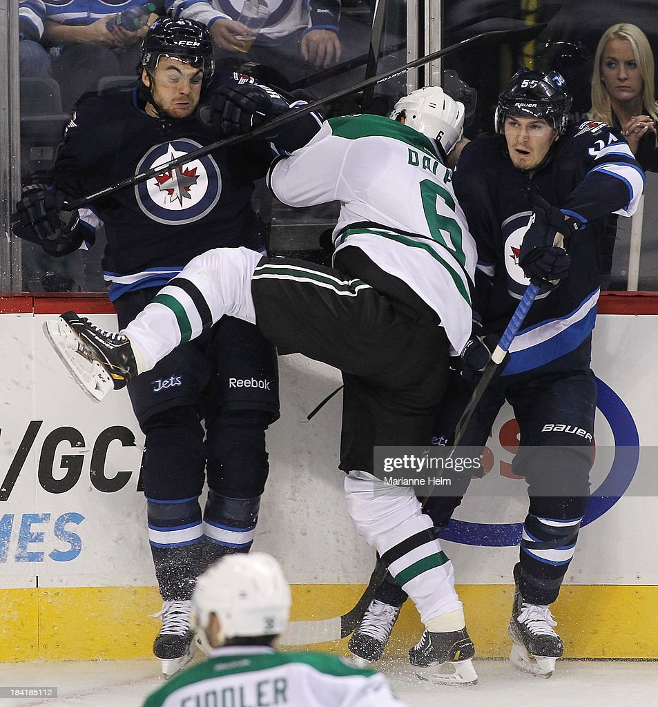 Trevor Daley #6 of the Dallas Stars collides with Michael Frolik #67 and Mark Scheifele #55 of the Winnipeg Jets in third-period action of an NHL game at the MTS Centre on October 11, 2013 in Winnipeg, Manitoba, Canada.