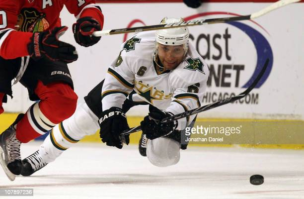 Trevor Daley of the Dallas Stars falls to ice after trying to knock the puck away from Patrick Sharp of the Chicago Blackhawks at the United Center...