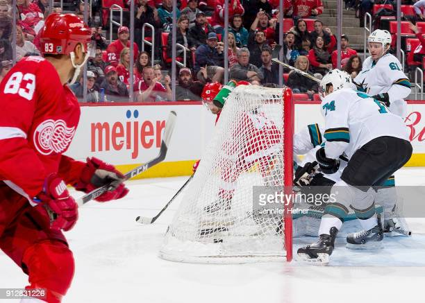 Trevor Daley of the Detroit Red Wings looks back on his goal as teammate Darren Helm follows and Martin Jones of the San Jose Sharks defends the net...
