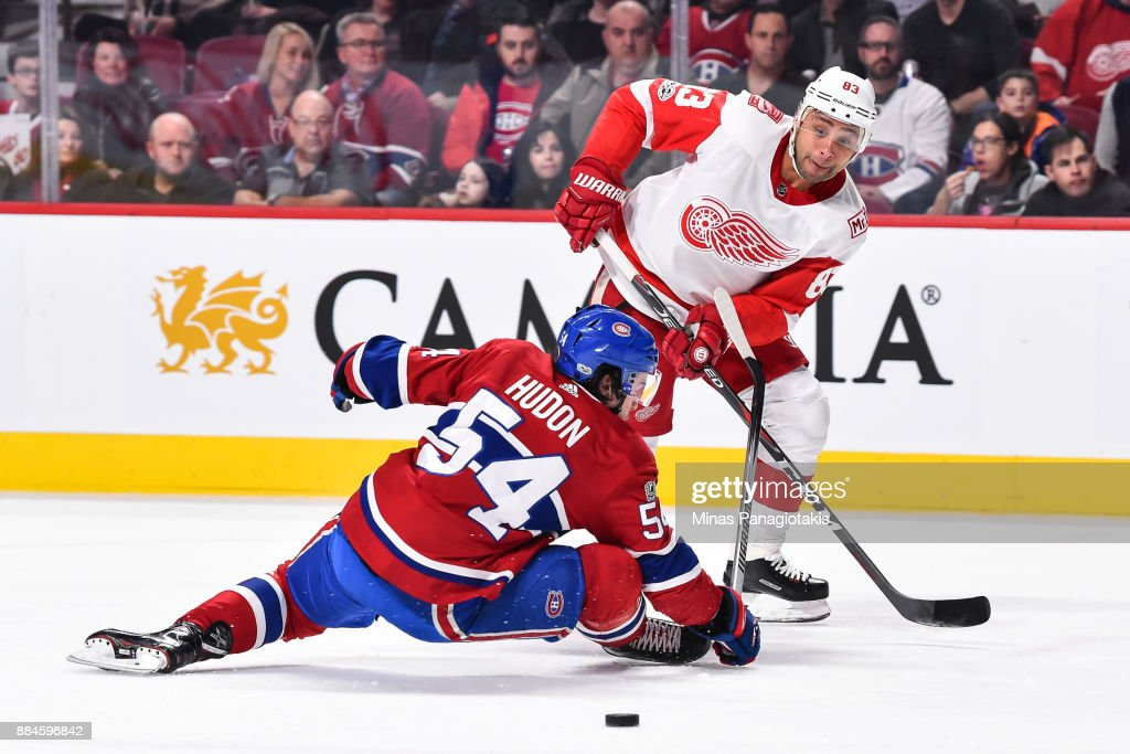 Trevor Daley #83 of the Detroit Red Wings plays the puck past Charles Hudon #54 of the Montreal Canadiens during the NHL game at the Bell Centre on December 2, 2017 in Montreal, Quebec, Canada.