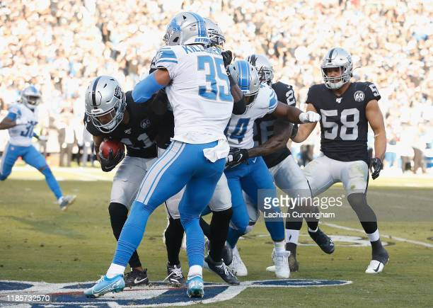 Trevor Davis of the Oakland Raiders is tackled by Miles Killebrew and Jalen Reeves-Maybin of the Detroit Lions at RingCentral Coliseum on November...