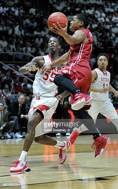 Trevor Dunbar of the Washington State Cougars jump for the basket around Delon Wright of the Utah Utes during the second half of Utah's 8664 win at...