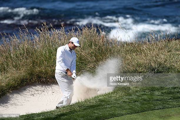 Trevor Immelman of South Africa plays lefthanded from a bunker on the seventh hole green during the first round of the 110th US Open at Pebble Beach...