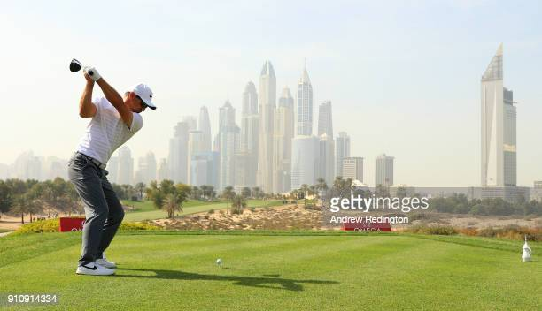 Trevor Immelman of South Africa tees off on the 8th hole with the city as a backdrop during day three of Omega Dubai Desert Classic at Emirates Golf...