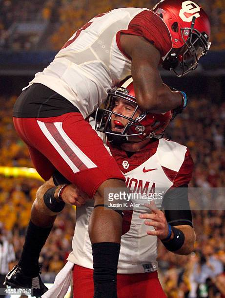 Trevor Knight of the Oklahoma Sooners celebrates with Durron Neal after catching a 4 yard touchdown pass in the second quarter during the game...