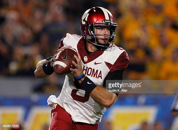 Trevor Knight of the Oklahoma Sooners drops back to pass in the first half during the game against the West Virginia Mountaineers on September 20...