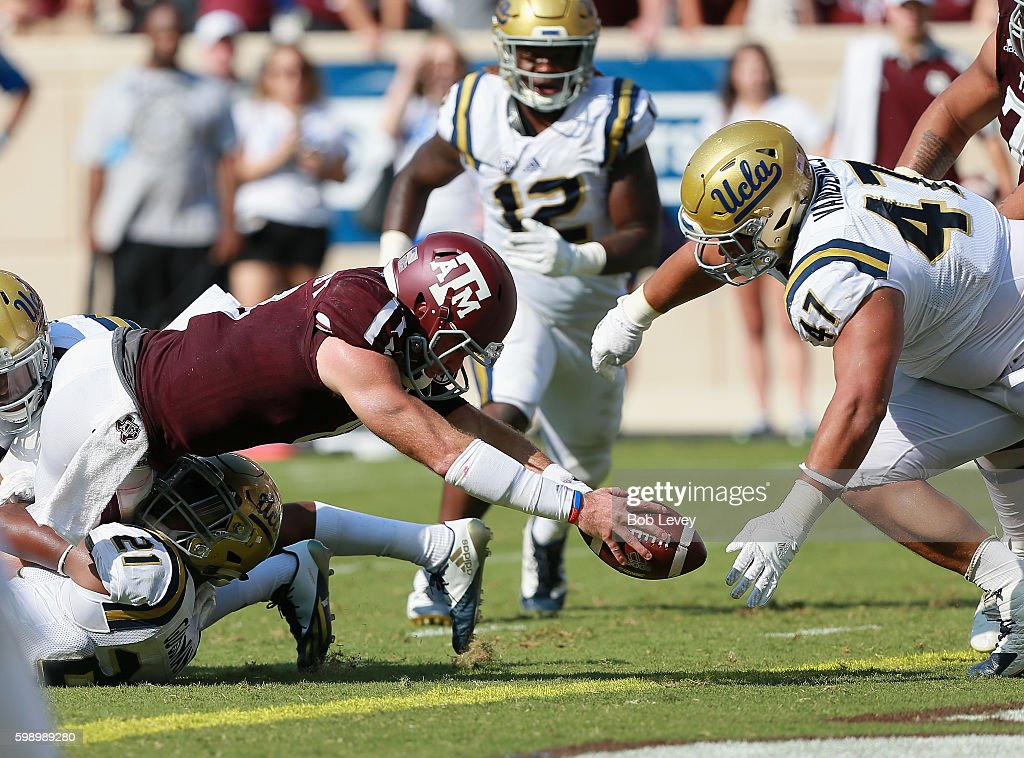 Trevor Knight #8 of the Texas A&M Aggies dives for a one yard score before Eddie Vanderdoes #47 of the UCLA Bruins or Jayon Brown can close in during the third quarter at Kyle Field on September 3, 2016 in College Station, Texas. Texas A&M won 31-24 in overtime.