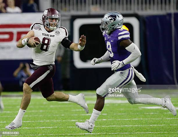 Trevor Knight of the Texas AM Aggies runs with the ball as he is pursued by Elijah Lee of the Kansas State Wildcats in the fourth quarter of the...