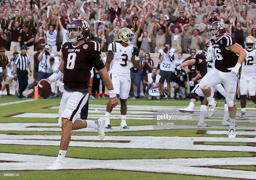 Trevor Knight #8 of the Texas A&M Aggies scores on a 1 yard run in overtime against the UCLA Bruins as Tanner Schorp #86 celebrates at Kyle Field on September 3, 2016 in College Station, Texas.