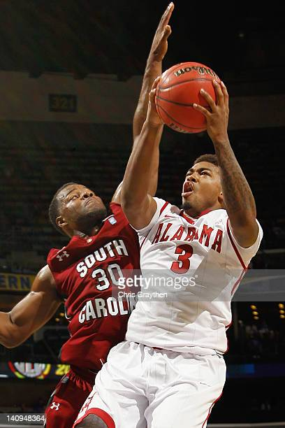 Trevor Lacey of the Alabama Crimson Tide shoots the ball over Lakeem Jackson of the South Carolina Gamecocks during the first round of the SEC...