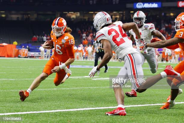 Trevor Lawrence of the Clemson Tigers carries the ball into the end zone for a touchdown against the Ohio State Buckeyes in the first quarter during...