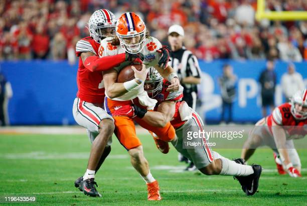 Trevor Lawrence of the Clemson Tigers is hit by Jeff Okudah and Tuf Borland of the Ohio State Buckeyes in the first half during the College Football...