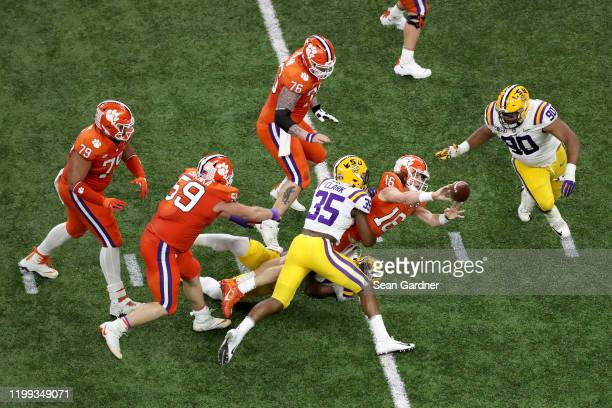 Trevor Lawrence of the Clemson Tigers is sacked by Damone Clark of the LSU Tigers in the College Football Playoff National Championship game at...