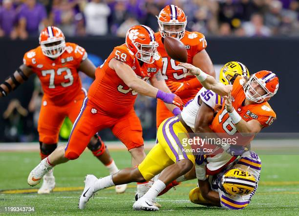 Trevor Lawrence of the Clemson Tigers is sacked by K'Lavon Chaisson of the LSU Tigers and Damone Clark of the LSU Tigers in the College Football...