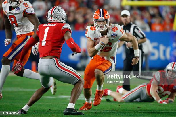 Trevor Lawrence of the Clemson Tigers runs the ball against Jeff Okudah of the Ohio State Buckeyes in the first half during the College Football...