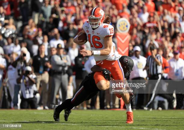 Trevor Lawrence of the Clemson Tigers runs with the ball against the South Carolina Gamecocks during their game at Williams-Brice Stadium on November...