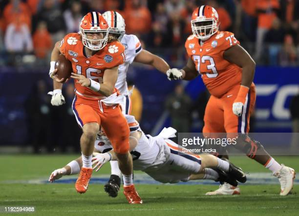 Trevor Lawrence of the Clemson Tigers runs with the ball against the Virginia Cavaliers during the ACC Football Championship game at Bank of America...
