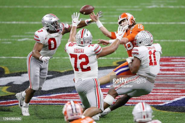 Trevor Lawrence of the Clemson Tigers throws an incomplete pass while pressured by Tyreke Smith of the Ohio State Buckeyes in the second half during...