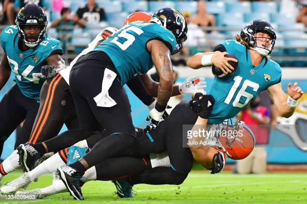 Trevor Lawrence of the Jacksonville Jaguars is sacked by Porter Gustin of the Cleveland Browns in the first quarter during a preseason game at TIAA...