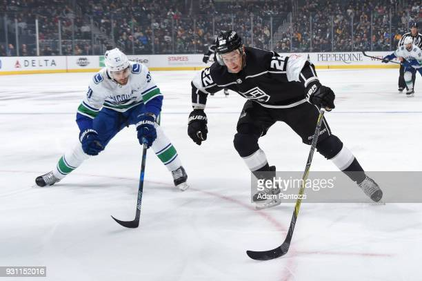 Trevor Lewis of the Los Angeles Kings handles the puck against Brandon Sutter of the Vancouver Canucks at STAPLES Center on March 12 2018 in Los...