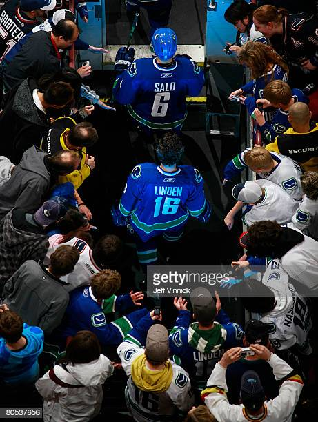 Trevor Linden and Sami Salo of the Vancouver Canucks walk onto the ice before the warmup before their game against the Calgary Flames at General...