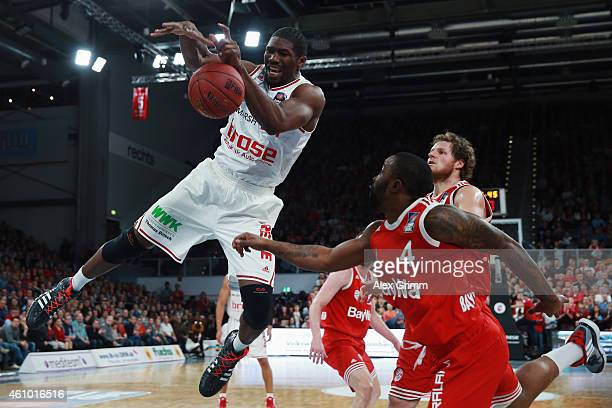 Trevor Mbakwe of Brose Baskets is challenged by Bo McCalebb and John Bryant of Muenchen during the Beko BBL basketball match between Brose Baskets...