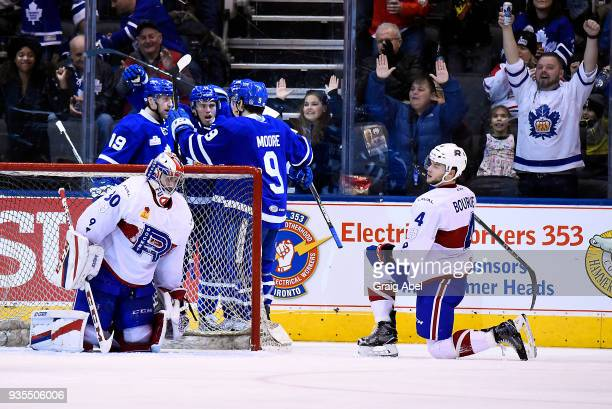 Trevor Moore and Chris Mueller of the Toronto Marlies celebrate a Marlie goal while goalie Zachary Fucale and Simon Bourque the Laval Rocket look on...