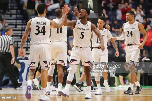 Trevor Moore of the Cincinnati Bearcats high fives Jarron Cumberland against the Nevada Wolf Pack during the first half in the second round of the...