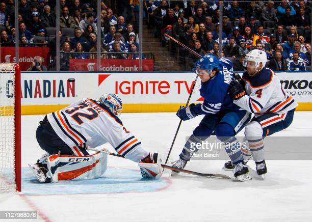 Trevor Moore of the Toronto Maple Leafs goes to the net against Kris Russell of the Edmonton Oilers and Anthony Stolarz during the third period at...