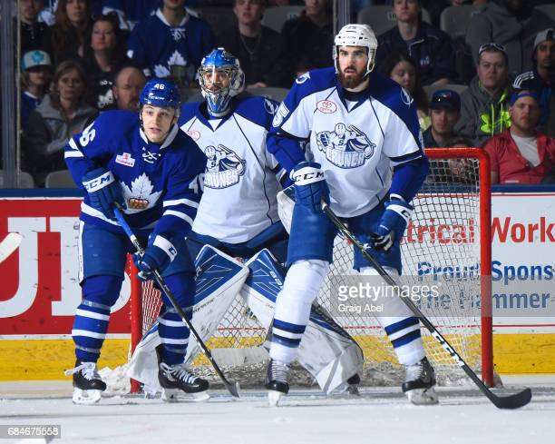 Trevor Moore of the Toronto Marlies gets into the crease with goalie Mike McKenna and Mathieu Brodeur of the Syracuse Crunch during game 6 action in...