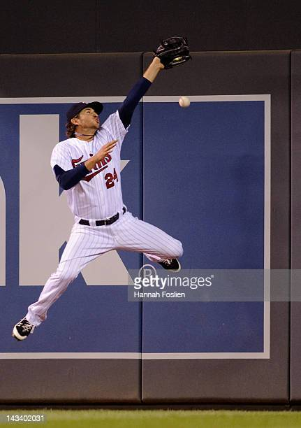 Trevor Plouffe of the Minnesota Twins misses a leaping catch in right field during the fifth inning against the Boston Red Sox on April 25 2012 at...