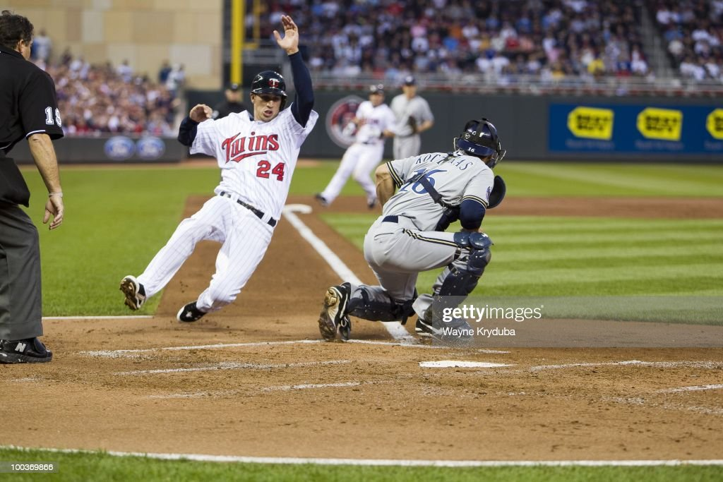 Trevor Plouffe #24 of the Minnesota Twins scores his first career run behind catcher George Kottaras #16 of the Milwaukee Brewers on May 21, 2010 at Target Field in Minneapolis, Minnesota. The Twins won 15-3.