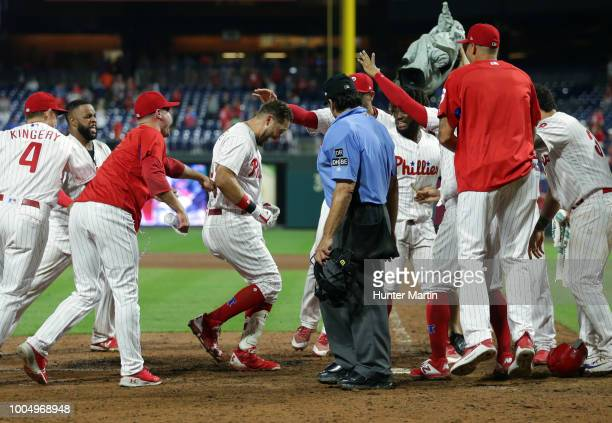 Trevor Plouffe of the Philadelphia Phillies is greeted by teammates at home plate after hitting a game winning walkoff threerun home run in the 16th...