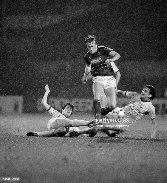Trevor Putney of Ipswich Town skips over tackles from Keven Brock and Gary Briggs of Oxford United during the Milk Cup 4th round match at Portman...