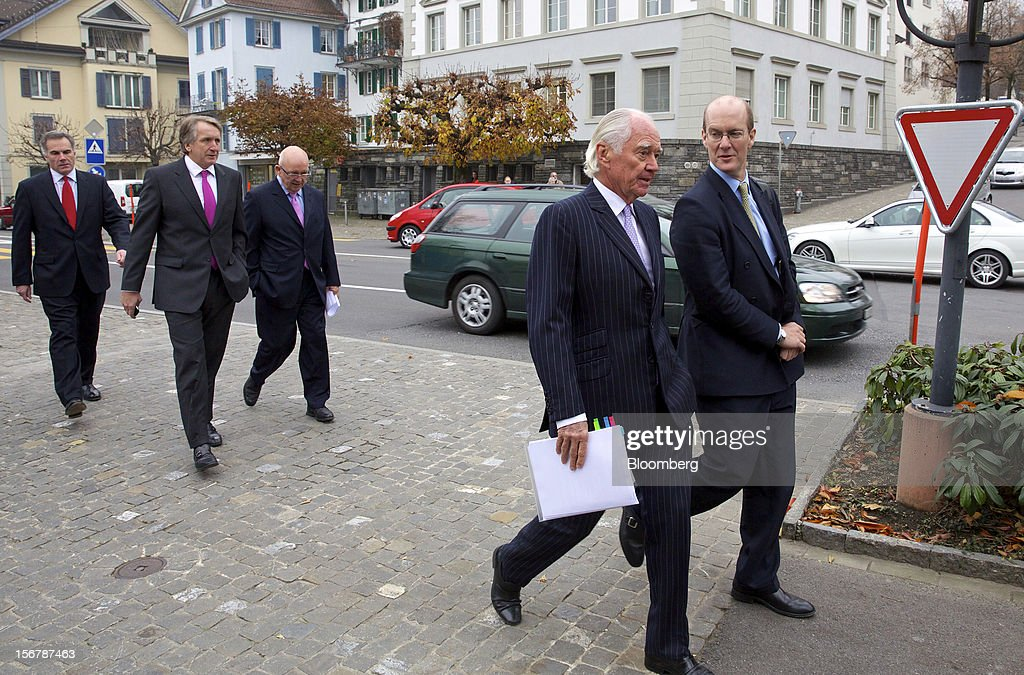 Trevor Reid, chief financial officer of Xstrata Plc, second left, and John Bond, chairman of Xstrata Plc, second right, arrive with colleagues for a shareholder's meeting in Zug, Switzerland, on Tuesday, Nov. 20, 2012. Xstrata shareholders voted to approve this year's biggest takeover, combining the Zug, Switzerland-based company's coal, copper, nickel and zinc mining assets with Glencore's cotton-to-crude oil commodities trading empire. Photographer: Gianluca Colla/Bloomberg via Getty Images