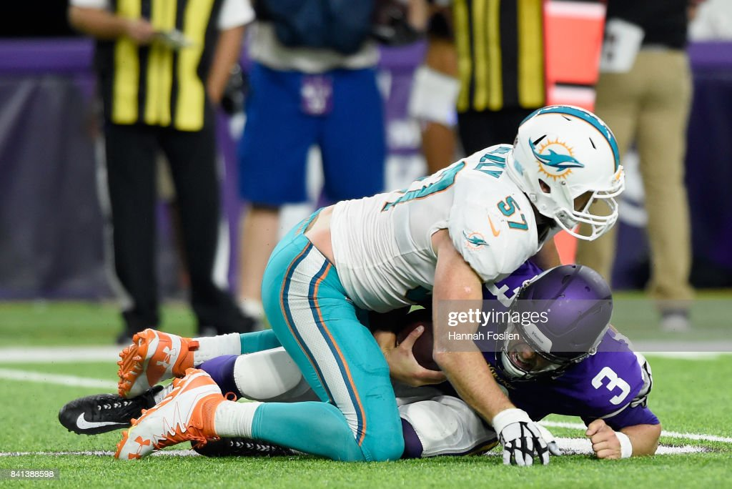 Trevor Reilly #57 of the Miami Dolphins tackles Mitch Leidner #3 of the Minnesota Vikings after a scramble during the fourth quarter in the preseason game on August 31, 2017 at U.S. Bank Stadium in Minneapolis, Minnesota. The Dolphins defeated the Vikings 30-9.
