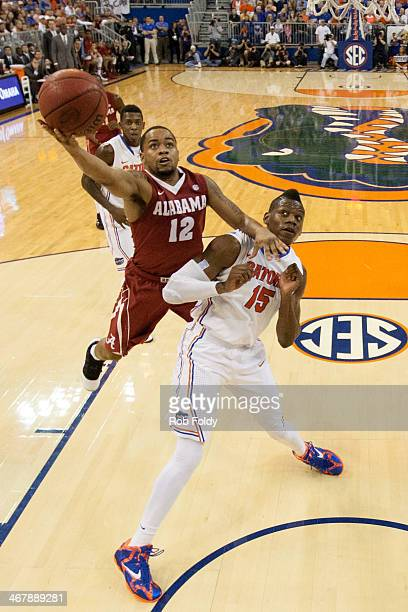 Trevor Releford of the Alabama Crimson Tide shoots the ball over Will Yeguete of the Florida Gators during the first half of the game at the Stephen...