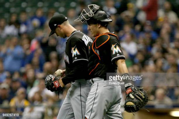 Trevor Richards and JT Realmuto of the Miami Marlins walk to the mound in the first inning against the Milwaukee Brewers at Miller Park on April 20...