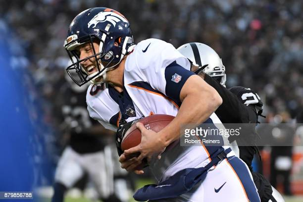 Trevor Siemian of the Denver Broncos is tackled by Reggie Nelson of the Oakland Raiders during their NFL game at OaklandAlameda County Coliseum on...